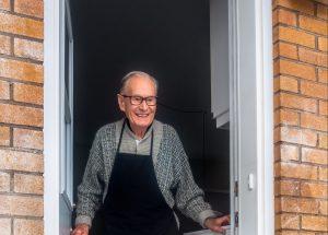 man opening door of house