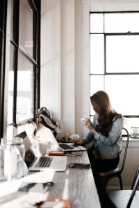 Woman drinking coffee and using a laptop in front on a large window