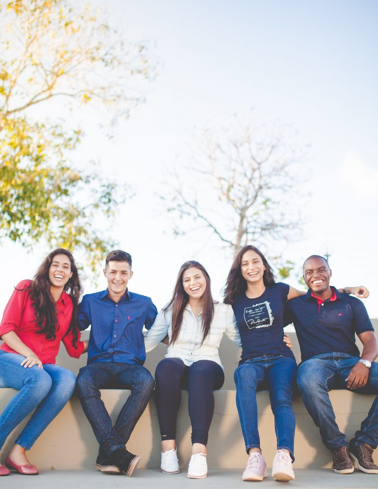 Group of people smiling sitting together on a bench